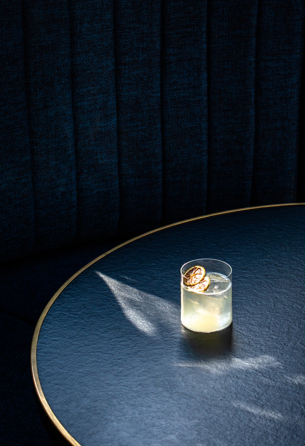 clear drinking glass with white liquid on blue round table