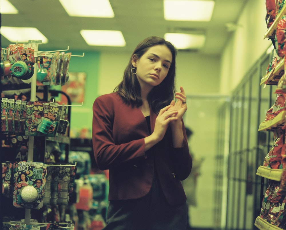 woman in brown long sleeve shirt standing near shelf