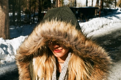 woman in black and brown fur coat standing on snow covered ground during daytime fur zoom background