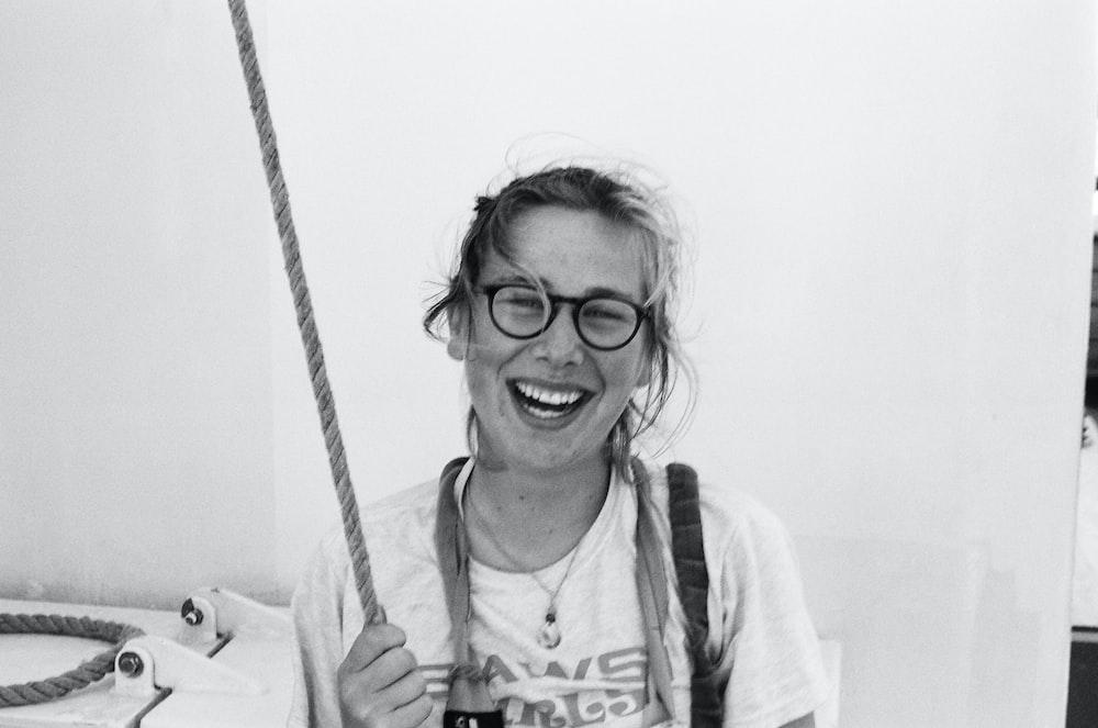 woman in white crew neck shirt wearing black framed eyeglasses