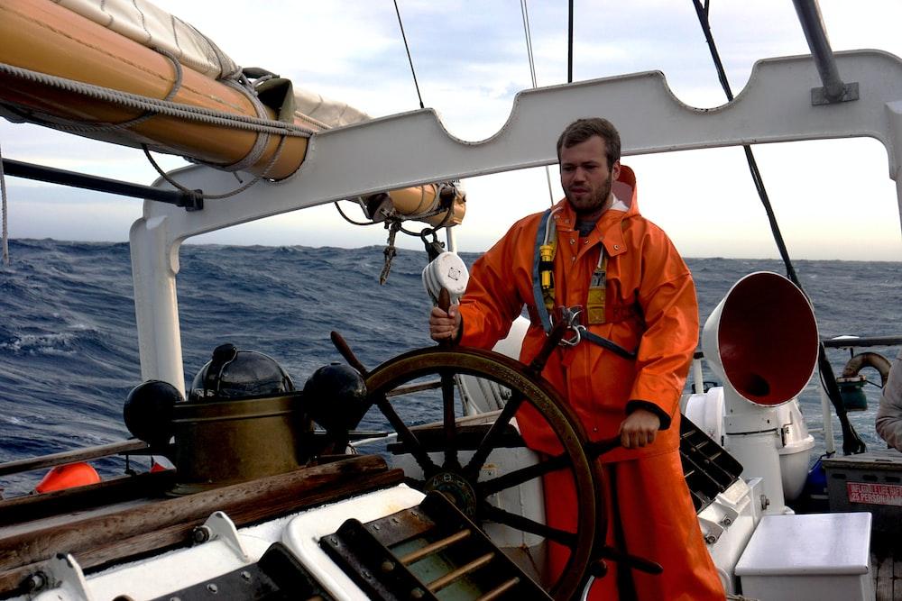 man in orange jacket standing on boat during daytime