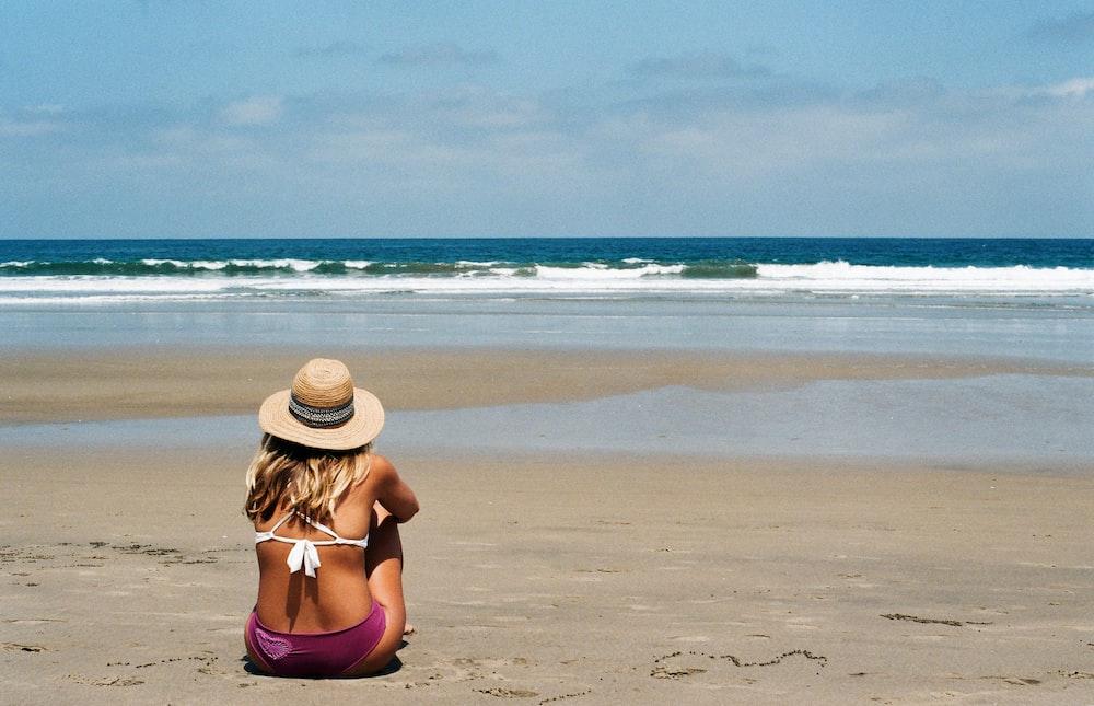 woman in purple bikini sitting on beach during daytime
