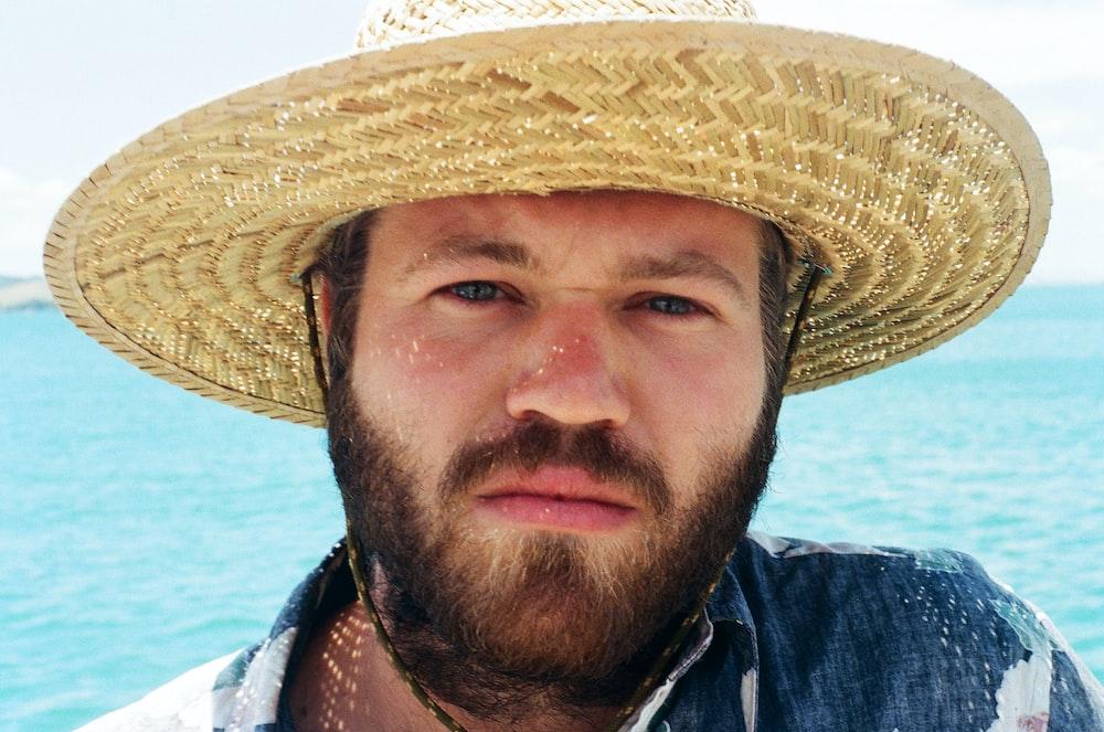 man in blue denim jacket wearing brown straw hat