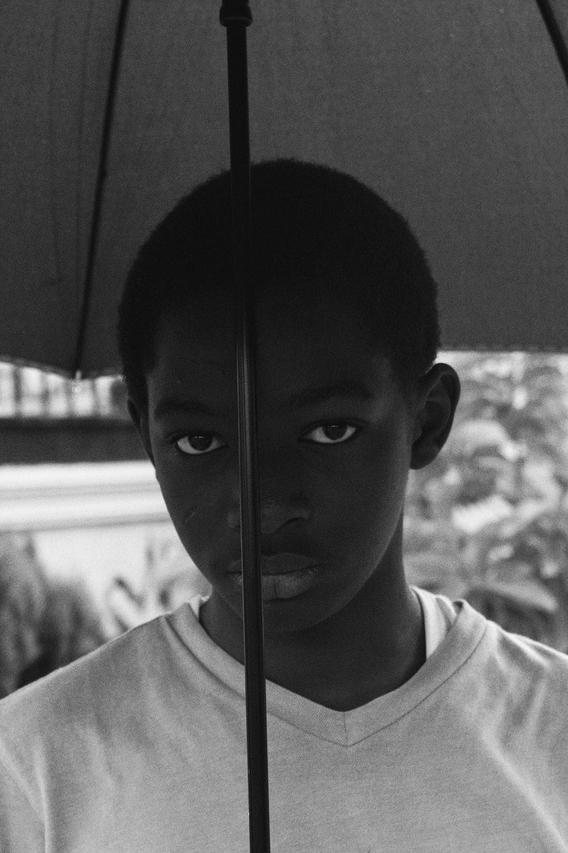 grayscale photo of boy in crew neck shirt holding umbrella