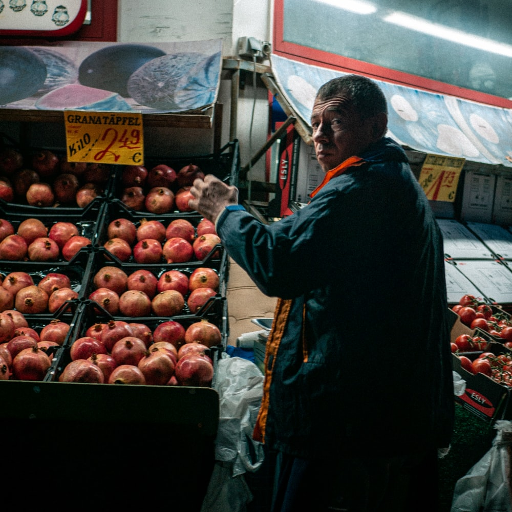 man in blue jacket standing in front of fruit stand during daytime