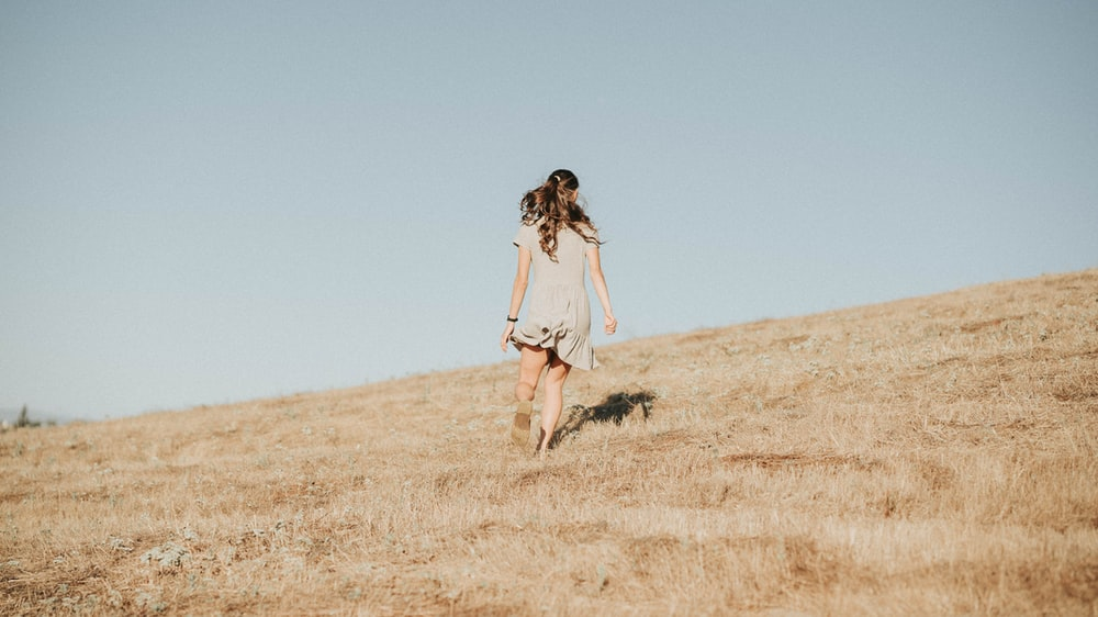 woman in white dress walking on brown grass field during daytime