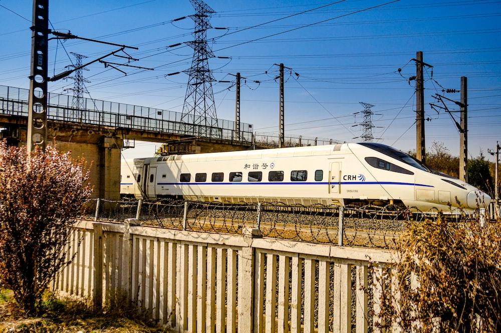 white train on rail tracks during daytime
