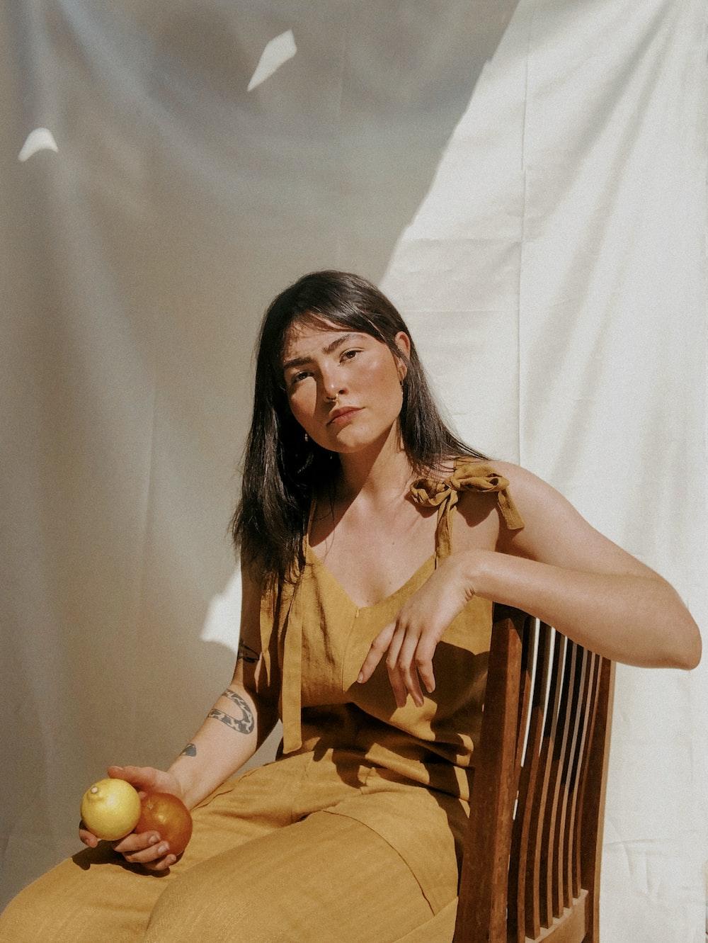 woman in orange sleeveless dress sitting on brown wooden chair
