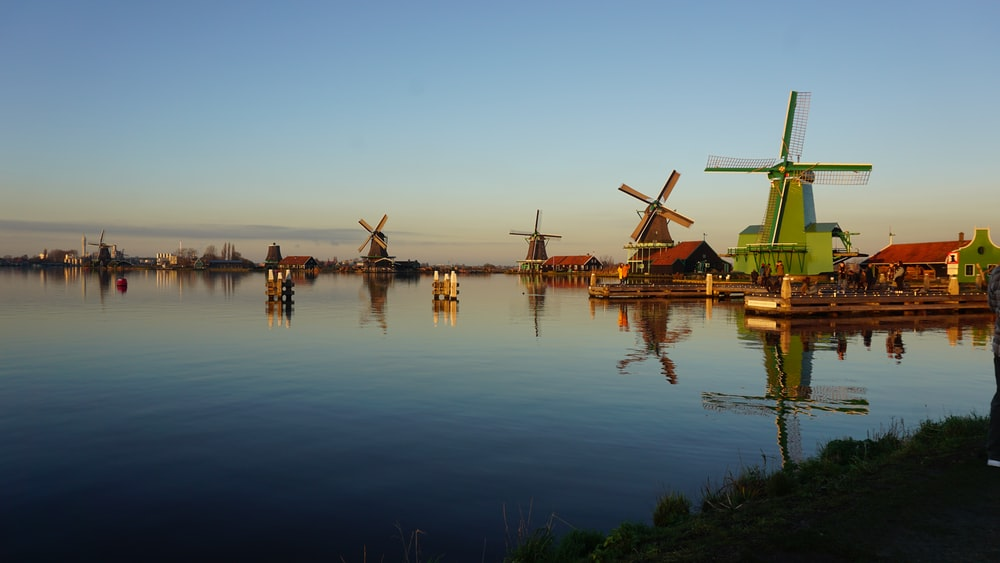 brown wooden windmill on green grass field near body of water during daytime