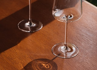 2 clear wine glasses on brown wooden table