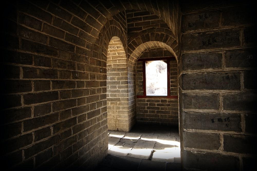 brown brick wall with red wooden door