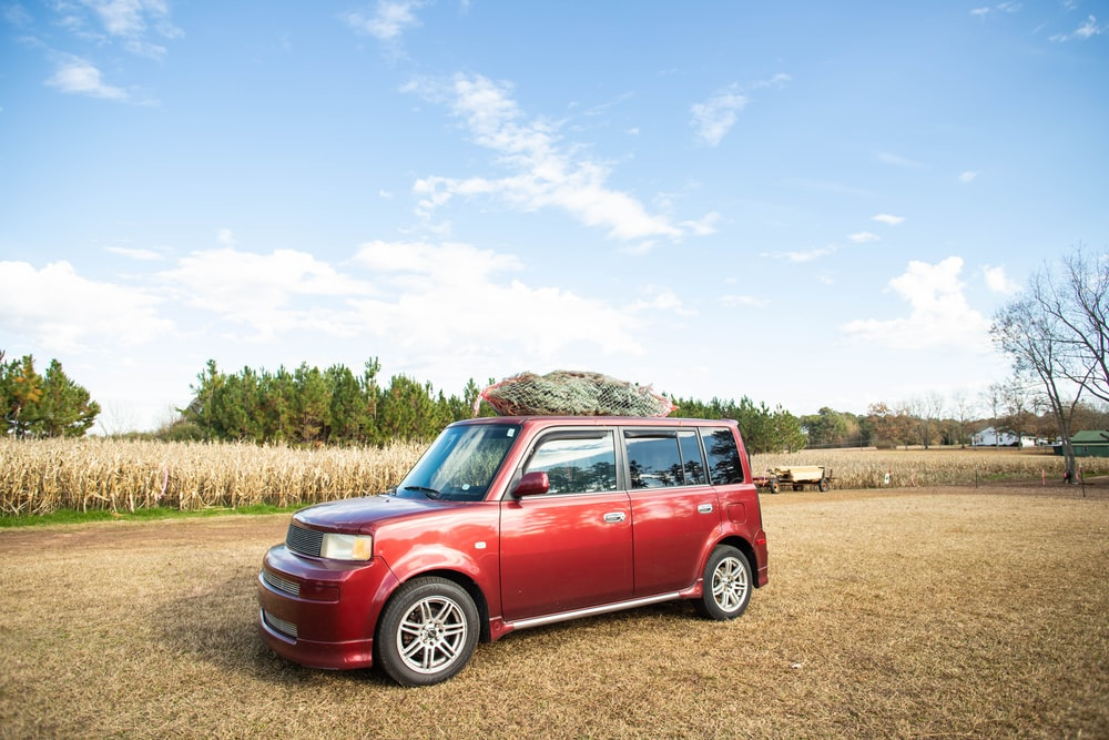 red suv on brown field under blue sky during daytime