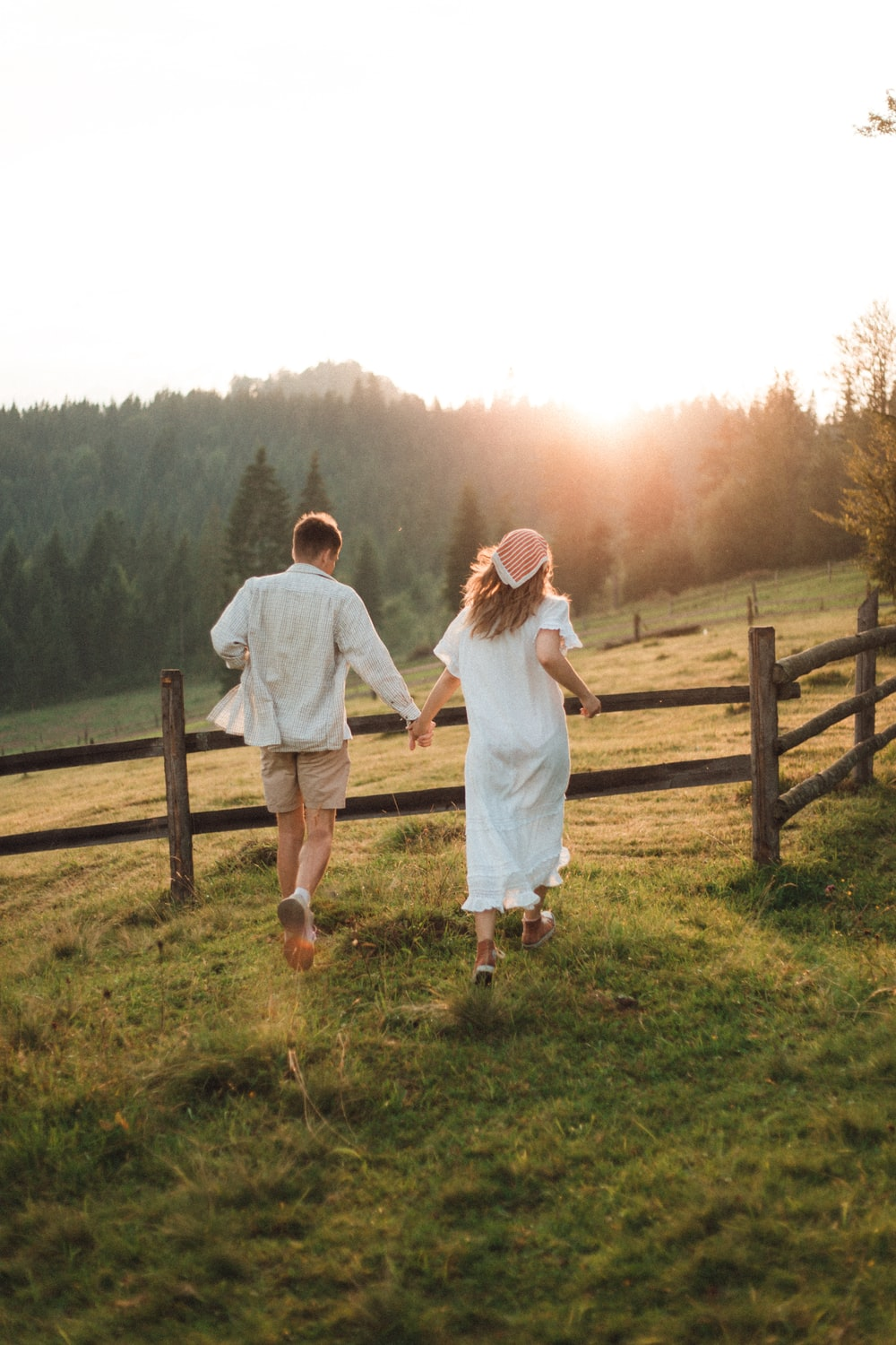 man and woman standing on green grass field during daytime