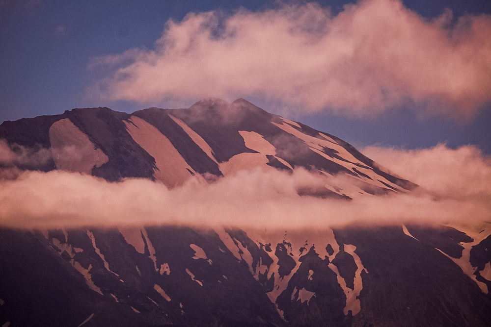 brown and white mountain under white clouds