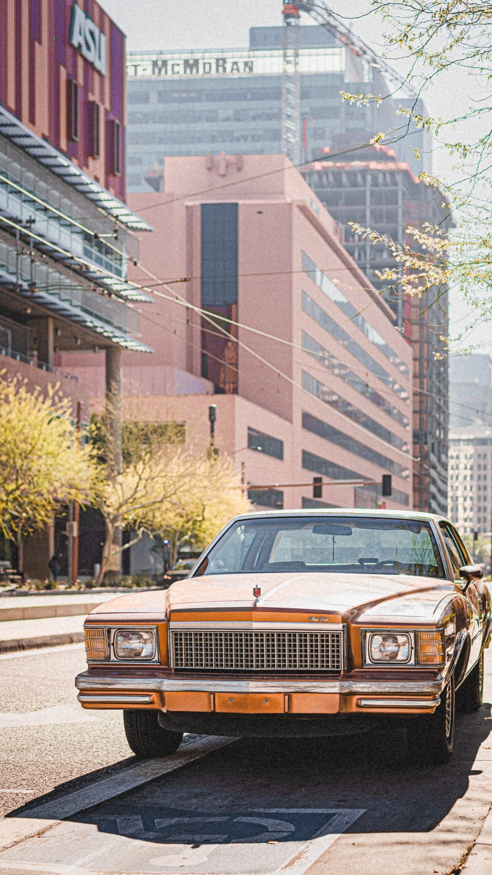 brown and white classic car parked near brown building during daytime