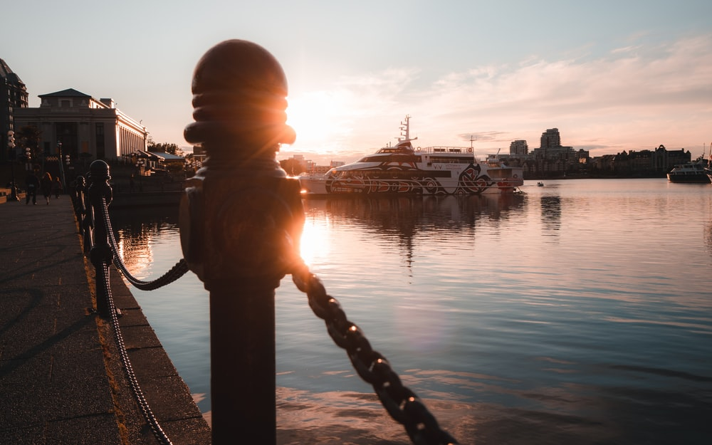silhouette of man standing on dock during sunset
