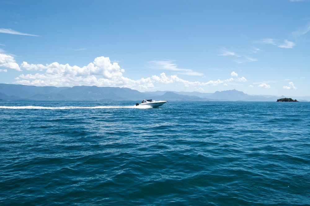 white and black boat on sea under blue sky during daytime