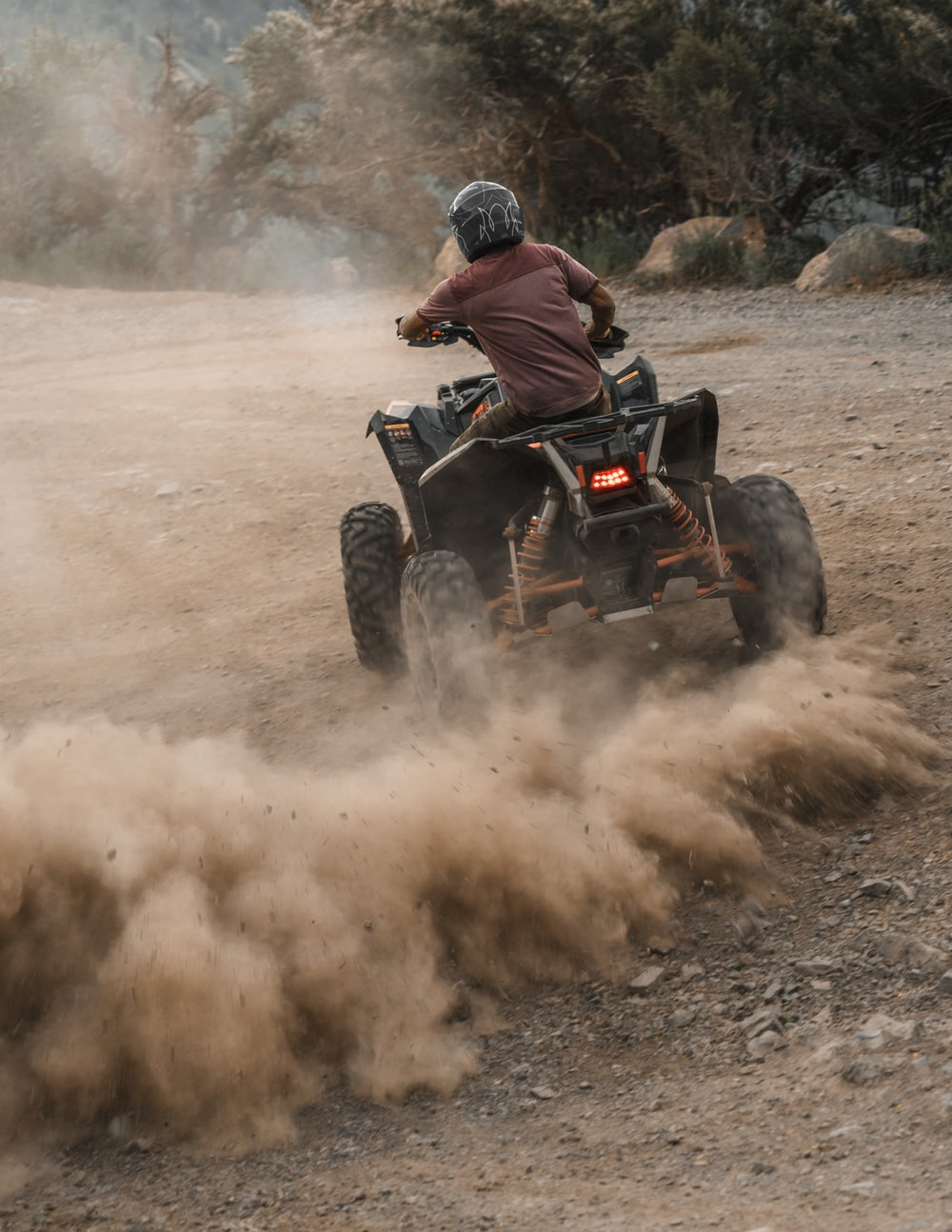 man riding atv on dirt road during daytime