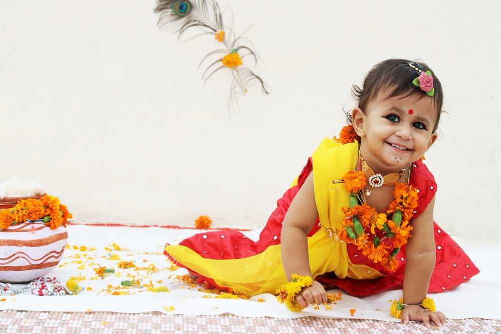 girl in yellow and red dress sitting on white and blue floral textile