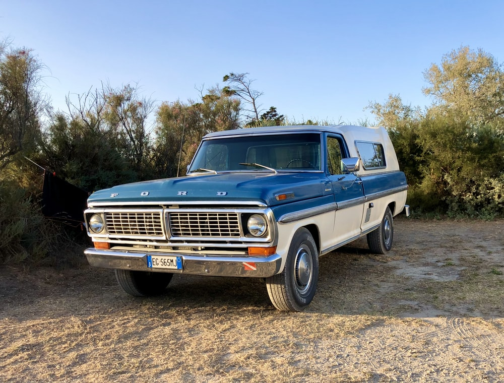 blue chevrolet crew cab pickup truck on brown dirt road during daytime