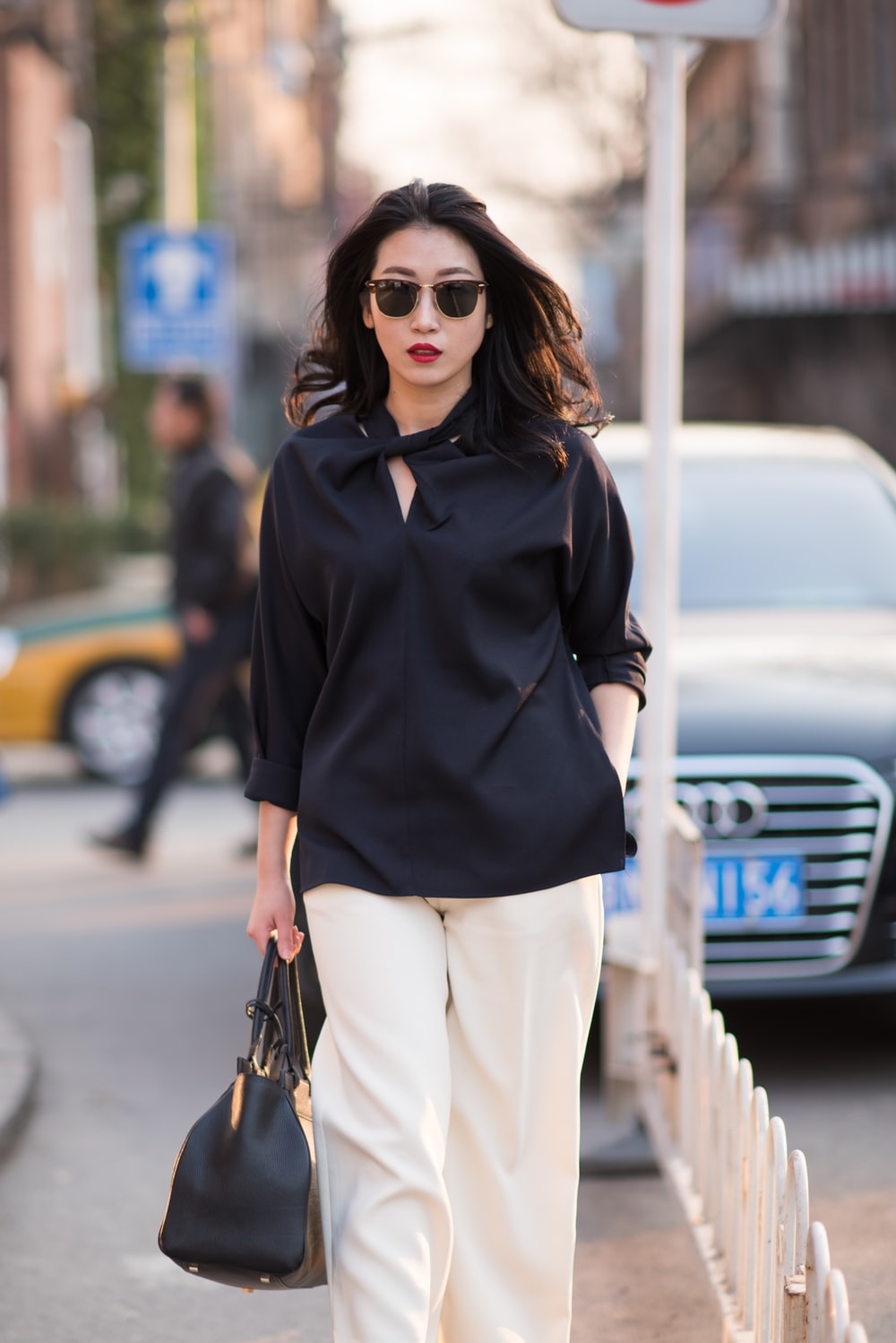 woman in black polo shirt and white pants wearing black sunglasses standing on road during daytime