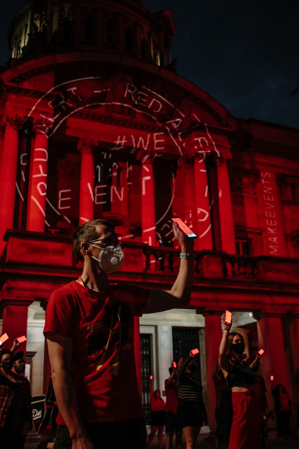 man in white crew neck t-shirt wearing black goggles standing near red building during nighttime