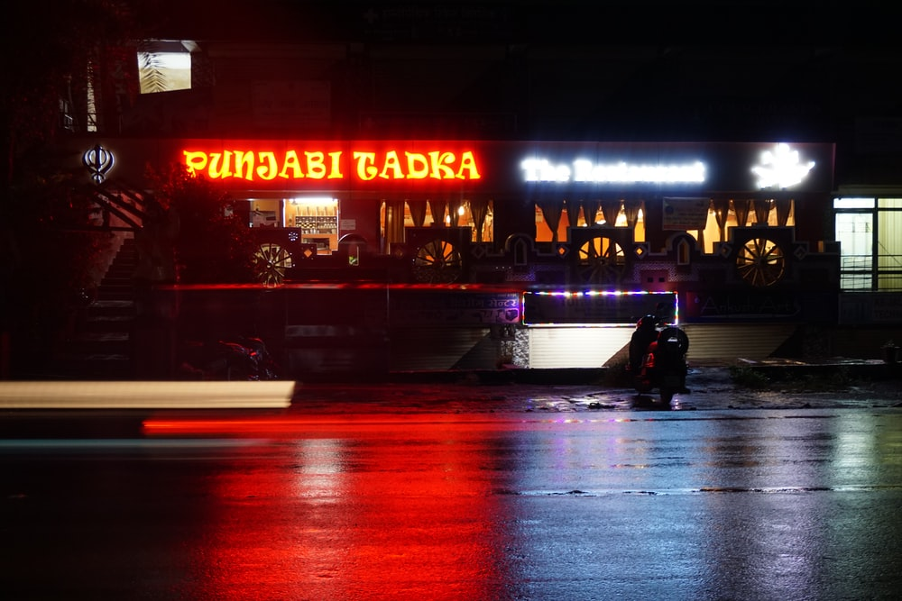 man in black jacket sitting on bench in front of store during night time