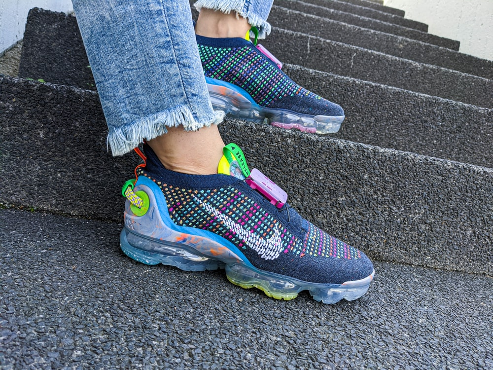 person wearing blue pink and green nike athletic shoes