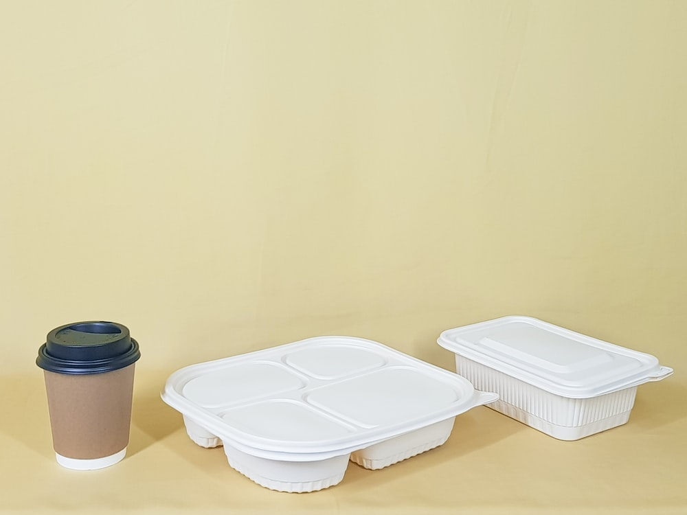 white plastic container on brown wooden table