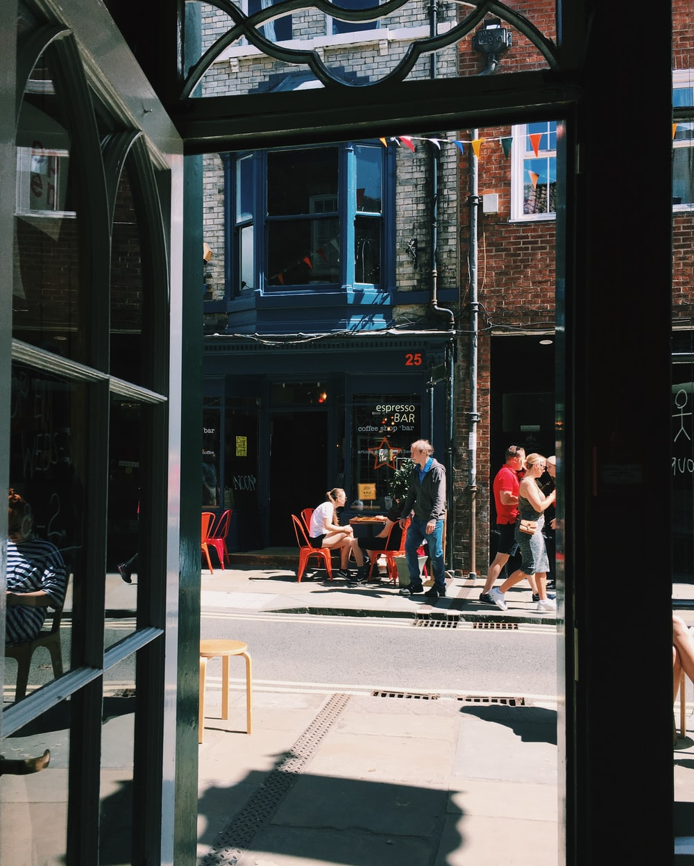 people sitting on bench in front of store during daytime
