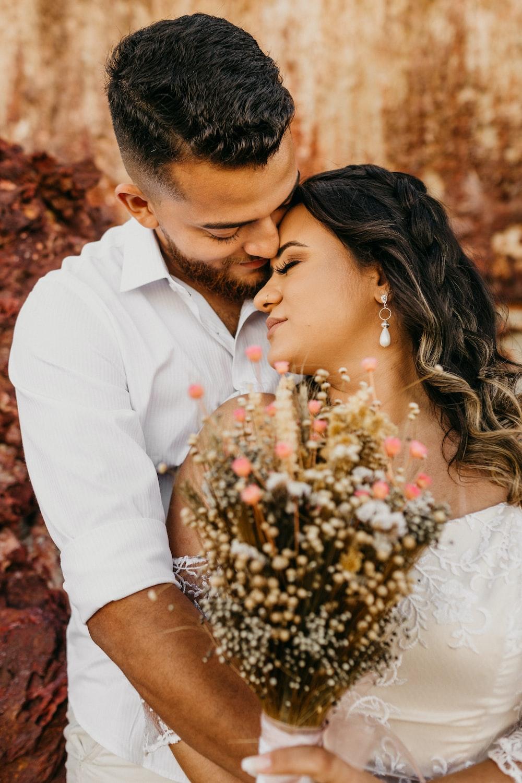 man in white dress shirt kissing womans hand