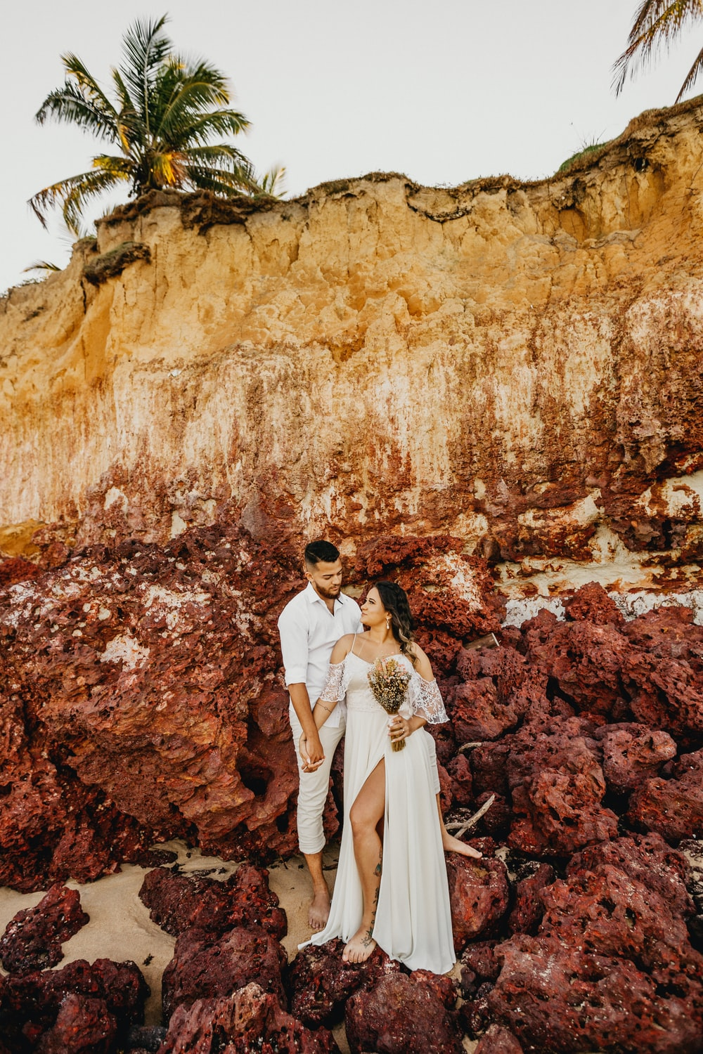 man and woman in white wedding dress standing in front of brown rock formation during daytime