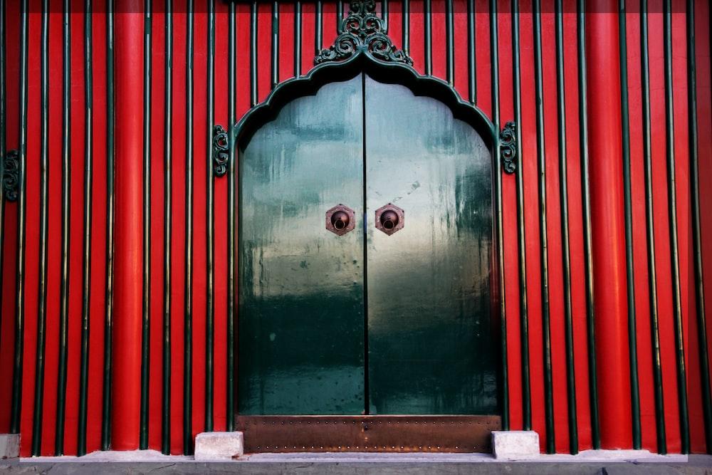 green wooden door with red and white wooden door