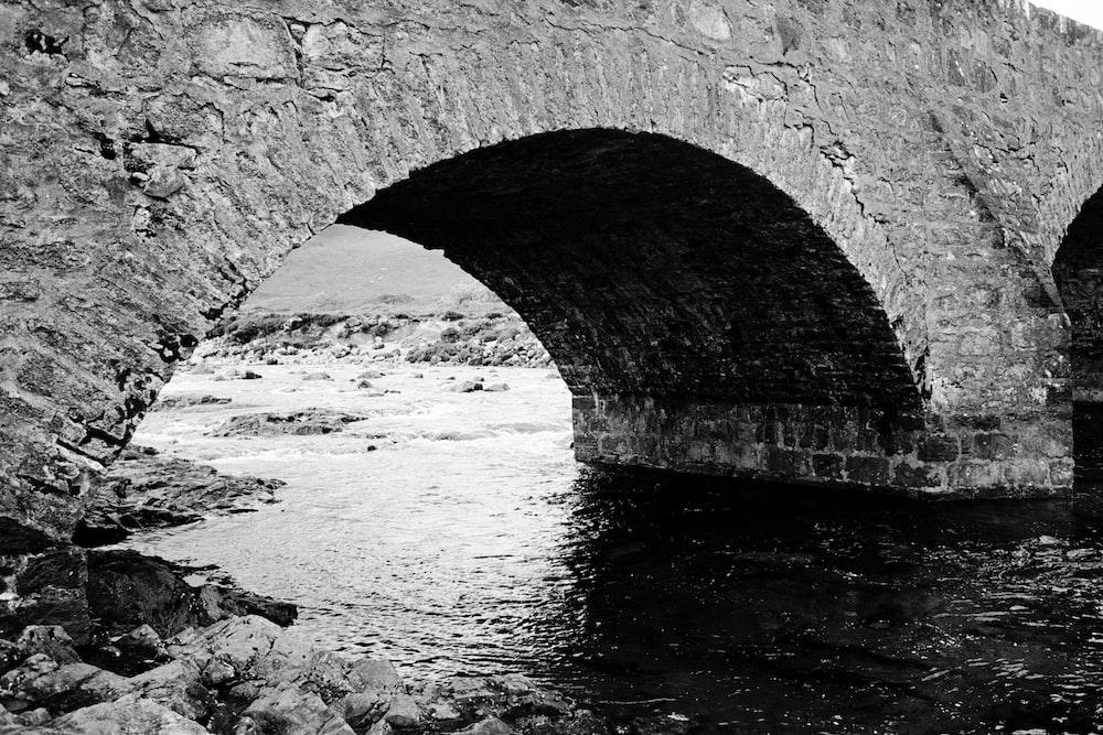 grayscale photo of body of water under bridge