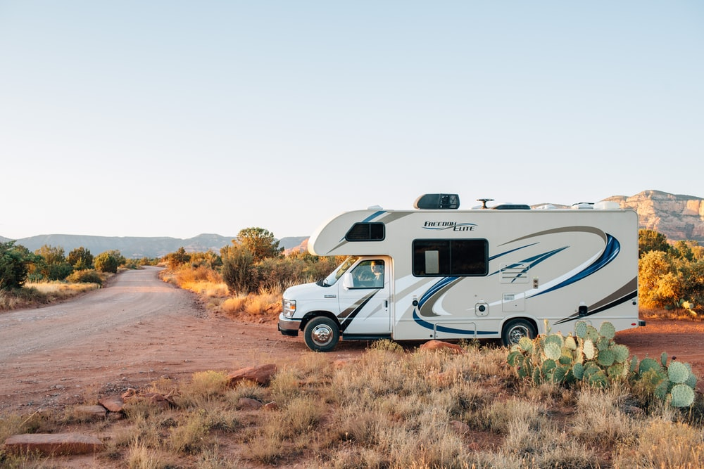 white and brown rv on brown grass field during daytime