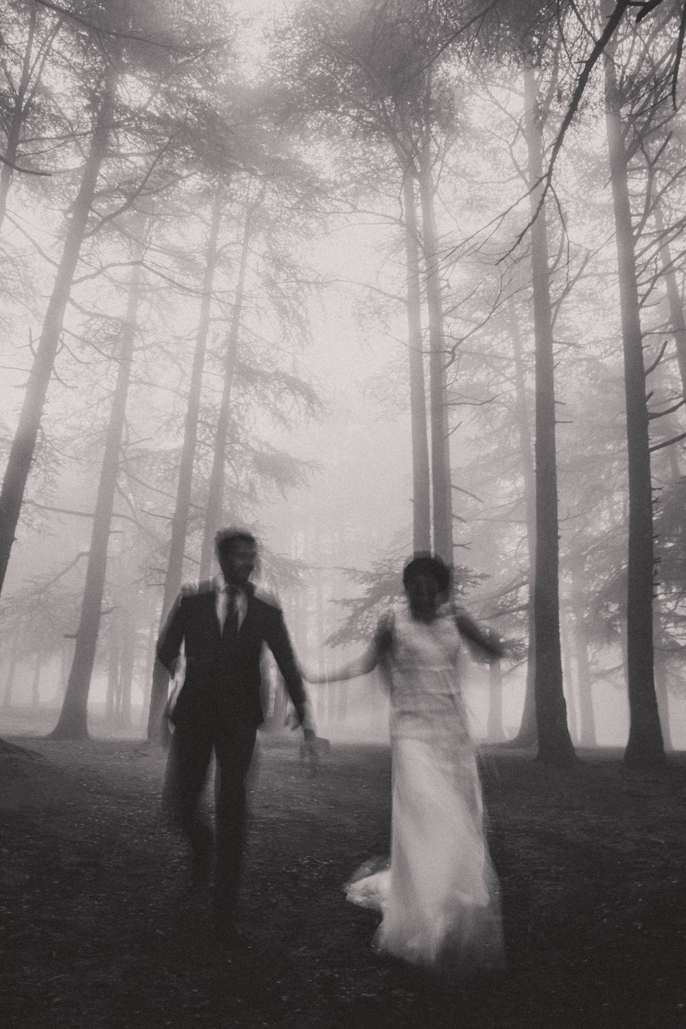 grayscale photo of man and woman walking on forest