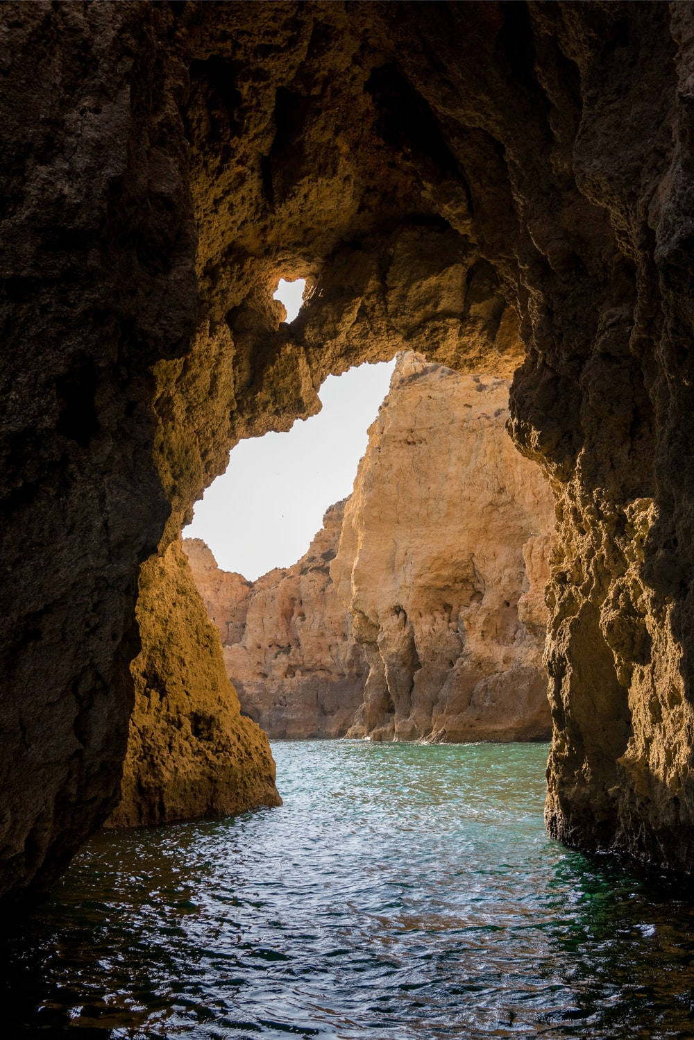 brown cave on blue sea water during daytime
