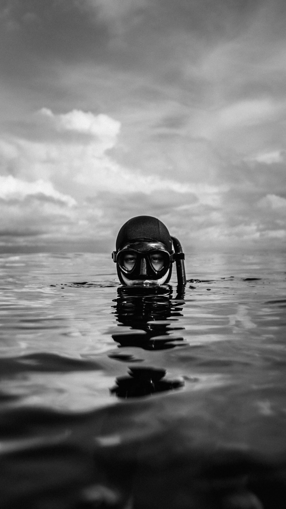 grayscale photo of person wearing goggles on water