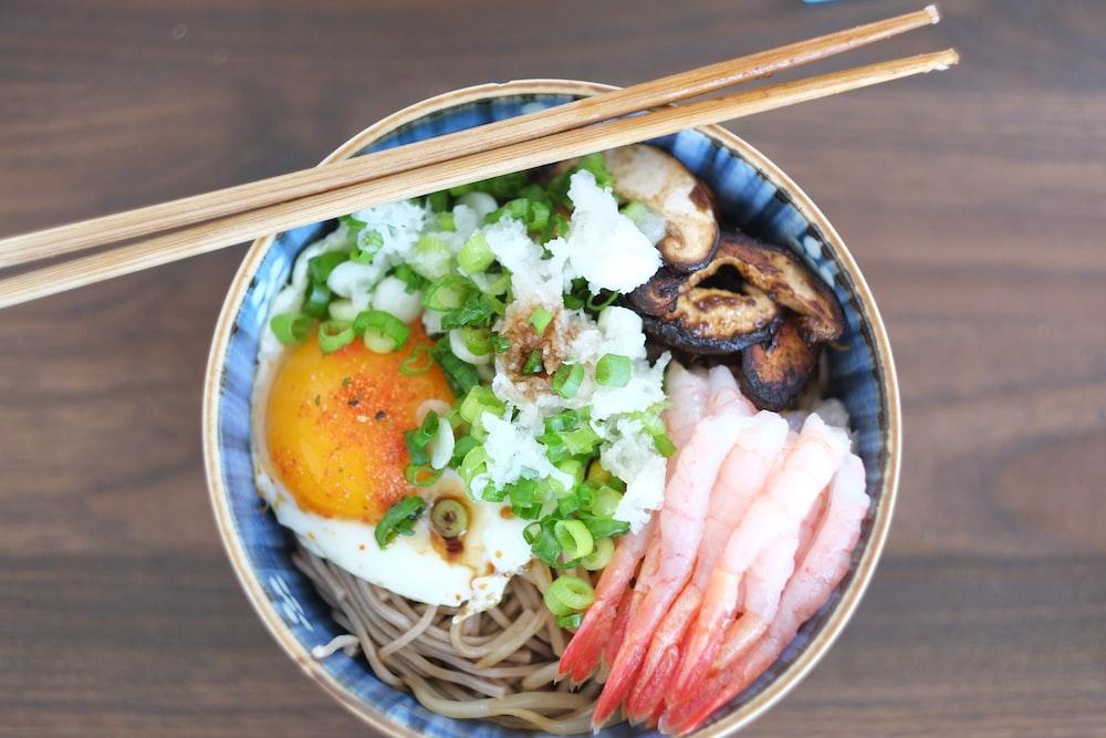 brown chopsticks on white and blue ceramic bowl