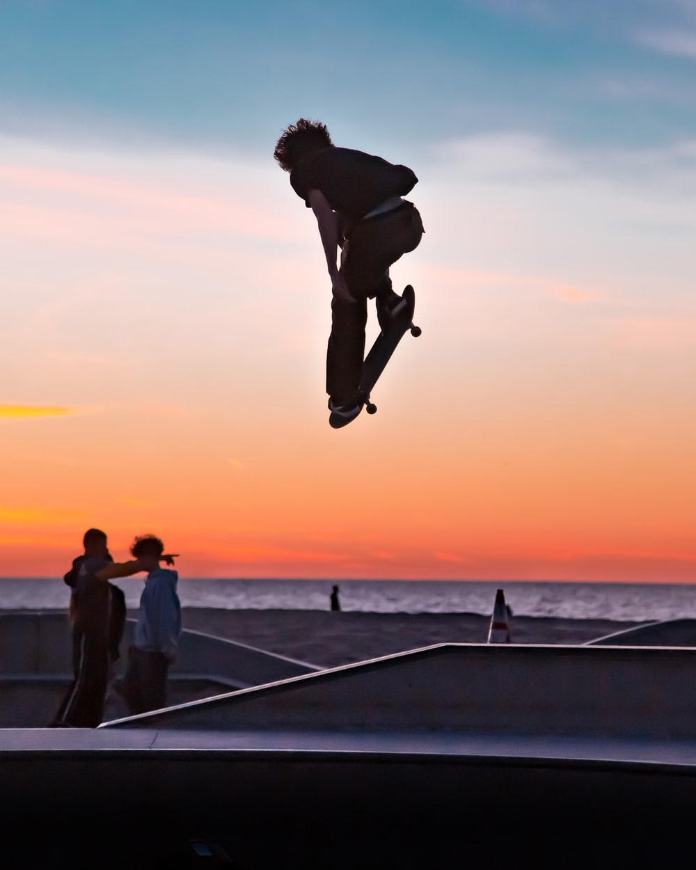man in black shorts and woman in white shirt jumping on the beach during sunset