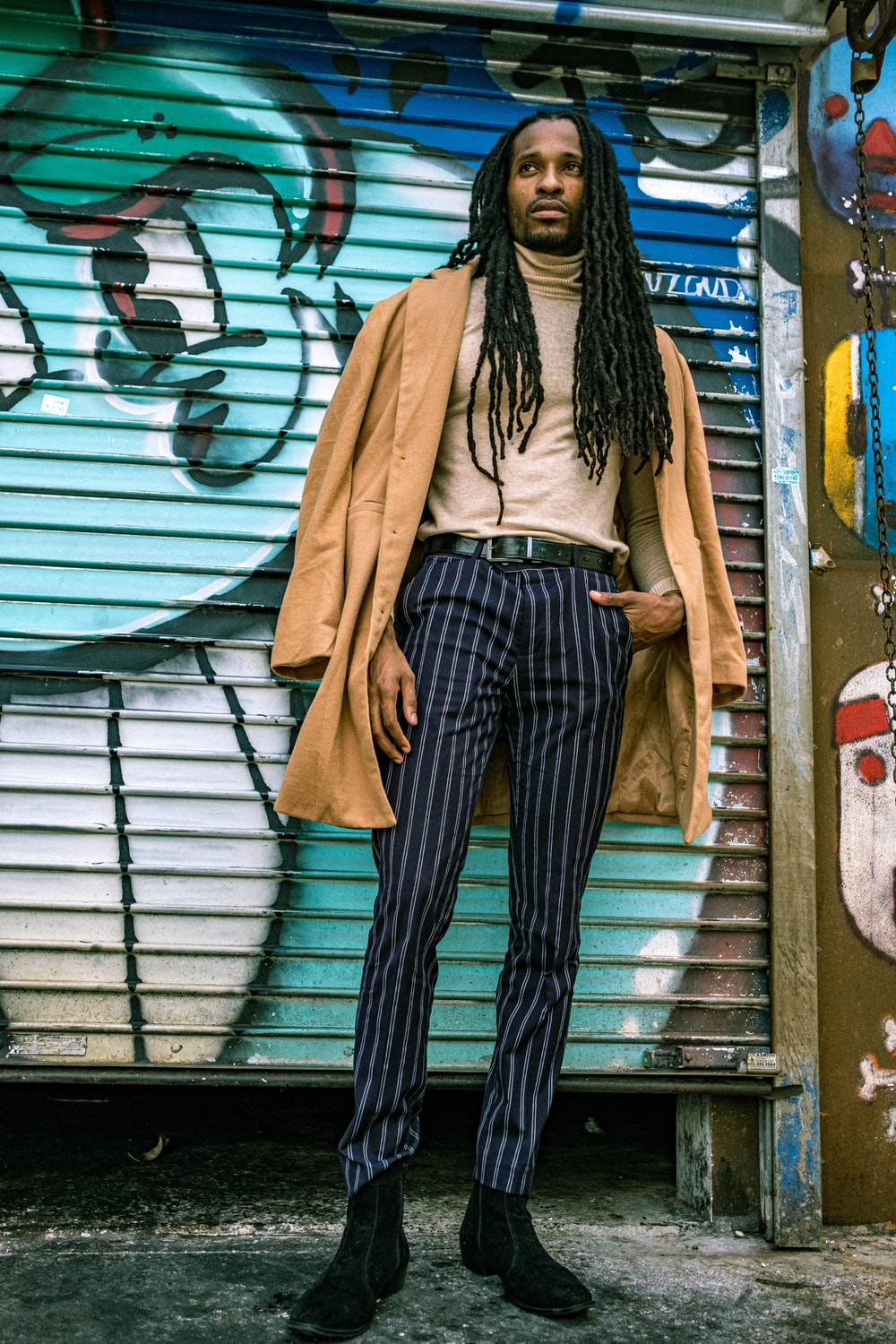 woman in brown coat and black and white striped pants standing beside white metal roll up