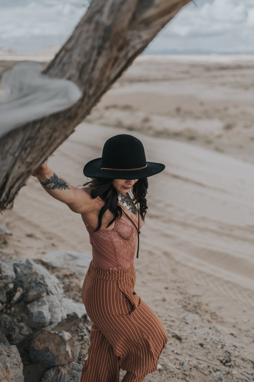 woman in brown and black stripe dress wearing black hat standing on brown sand during daytime