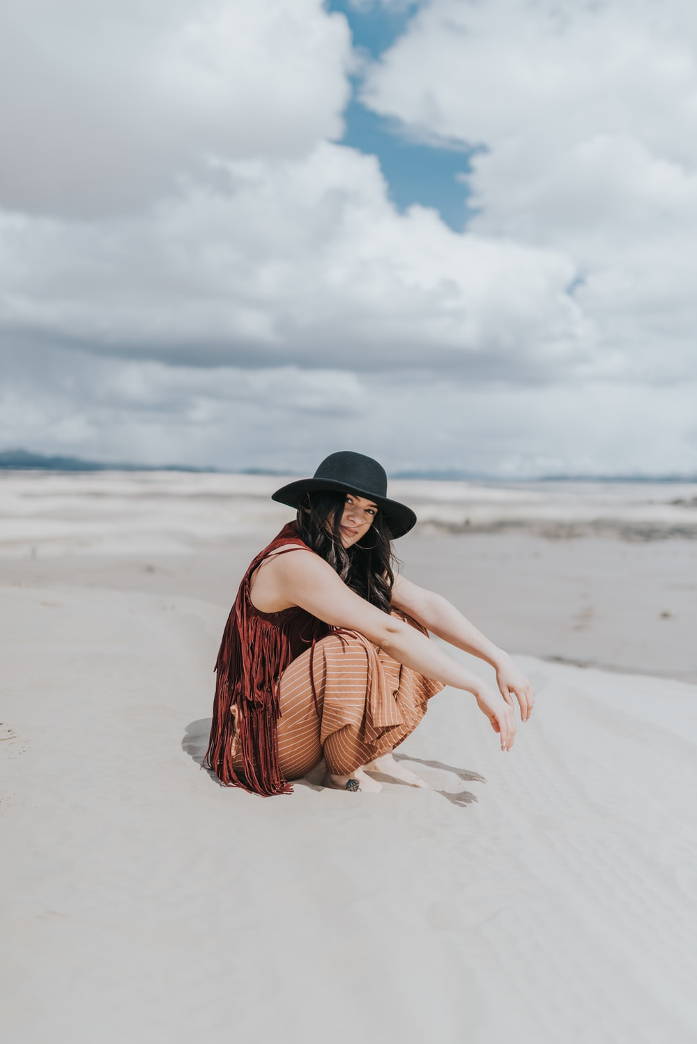 woman in brown and black plaid dress shirt and black fedora hat sitting on beach during