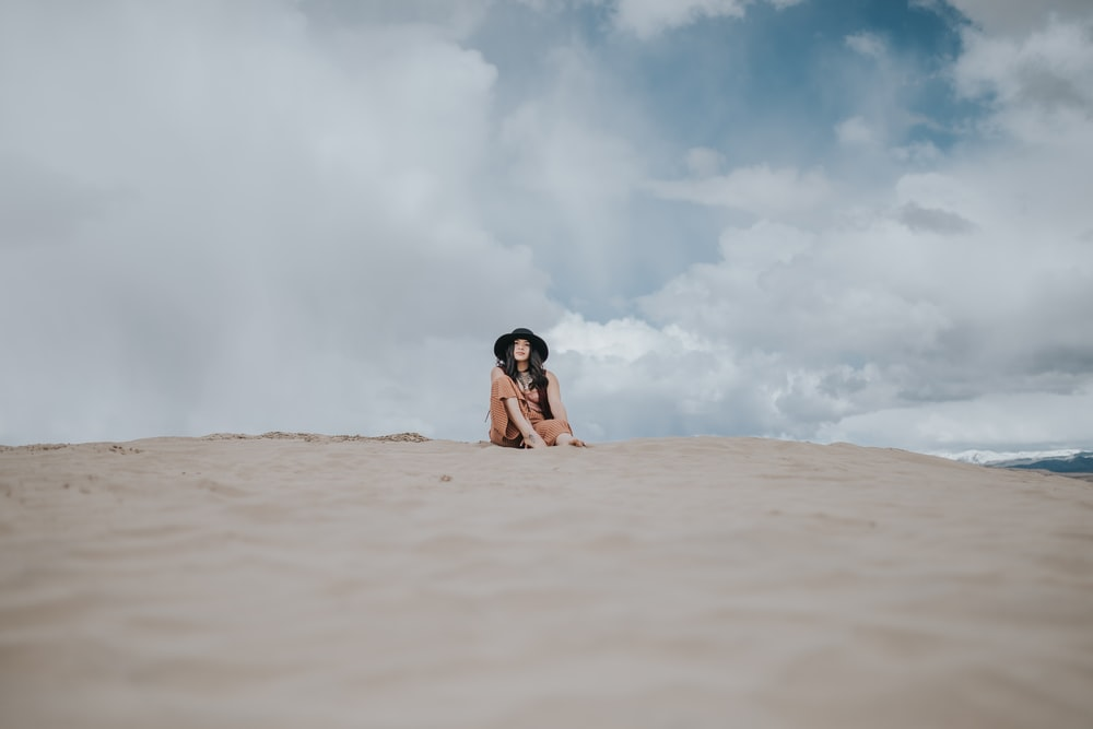 woman in black bikini lying on brown sand under white clouds during daytime