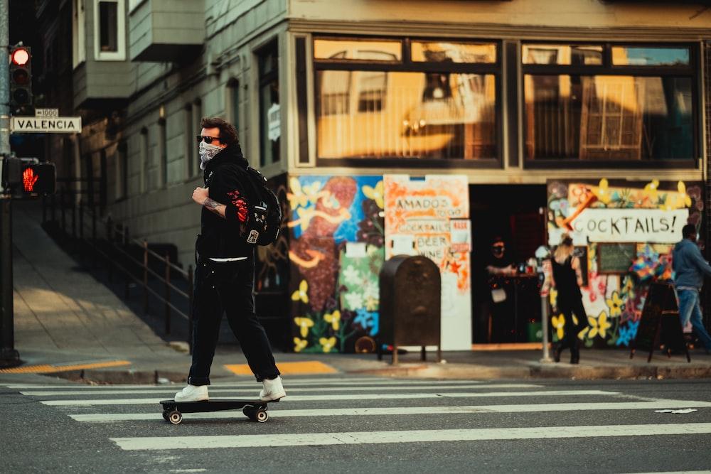 man in black jacket and black pants walking on pedestrian lane during daytime