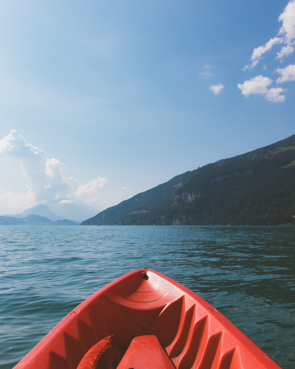 red kayak on sea near mountain under blue sky during daytime