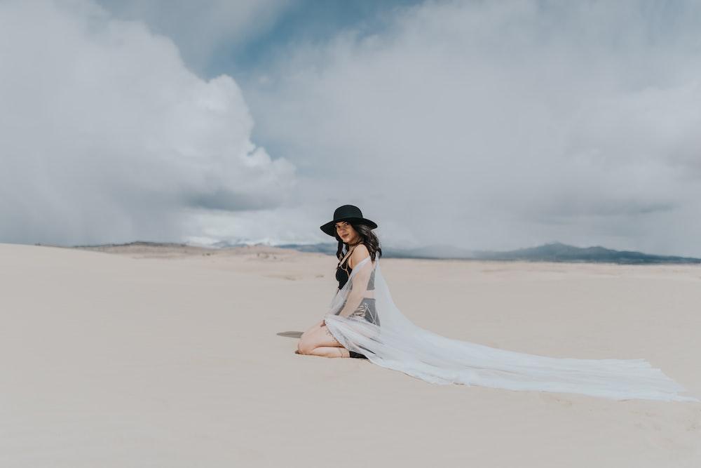 woman in white dress walking on sand during daytime