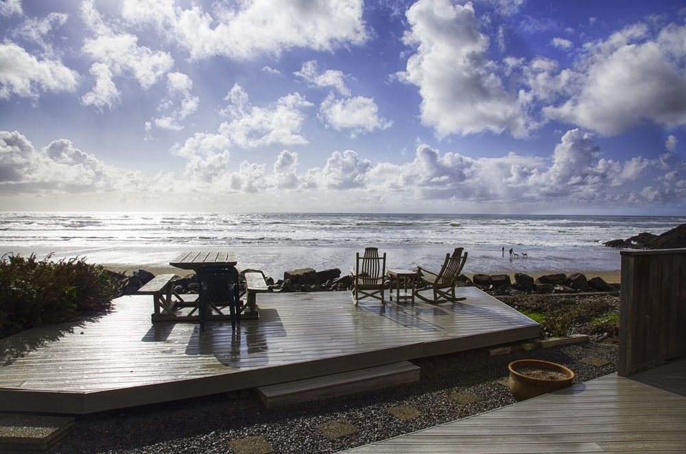 brown wooden table and chairs on beach during daytime