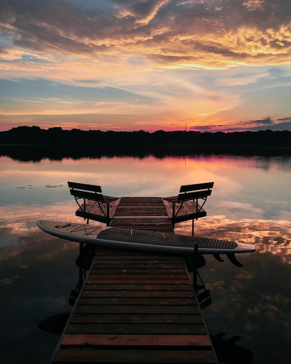 brown wooden bench on dock during sunset