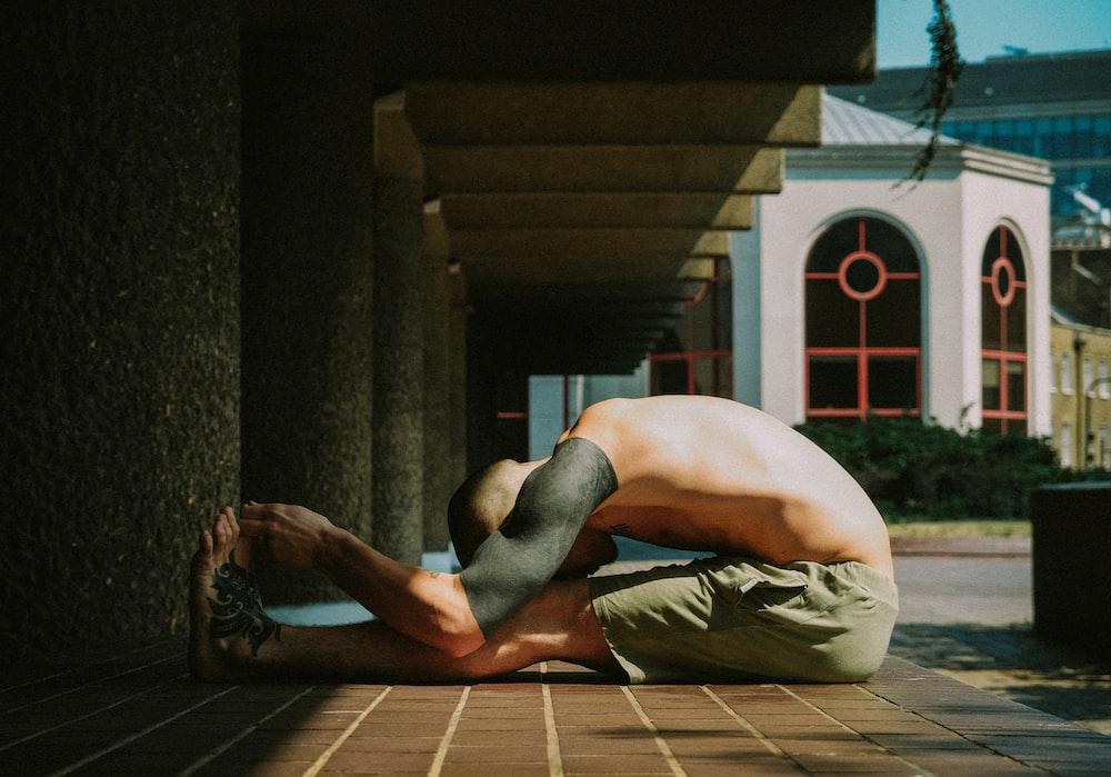 man in white shorts sitting on brown wooden floor